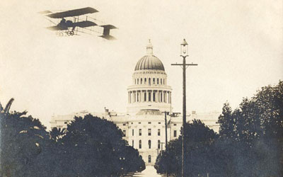 East side of the State Capitol showing the dome and entrance with an airplane flying overhead circa 1908