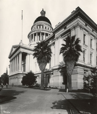 Southwest side of the State Capitol with men painting the dome circa 1910